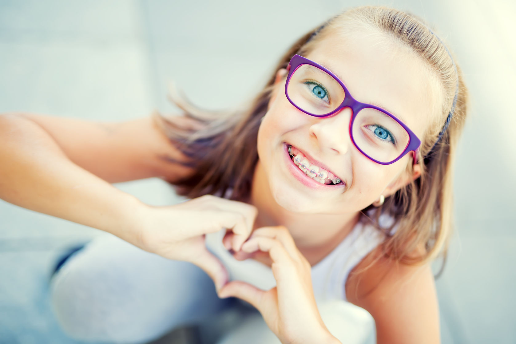 62296726 - smiling little girl in with braces and glasses showing heart with hands.