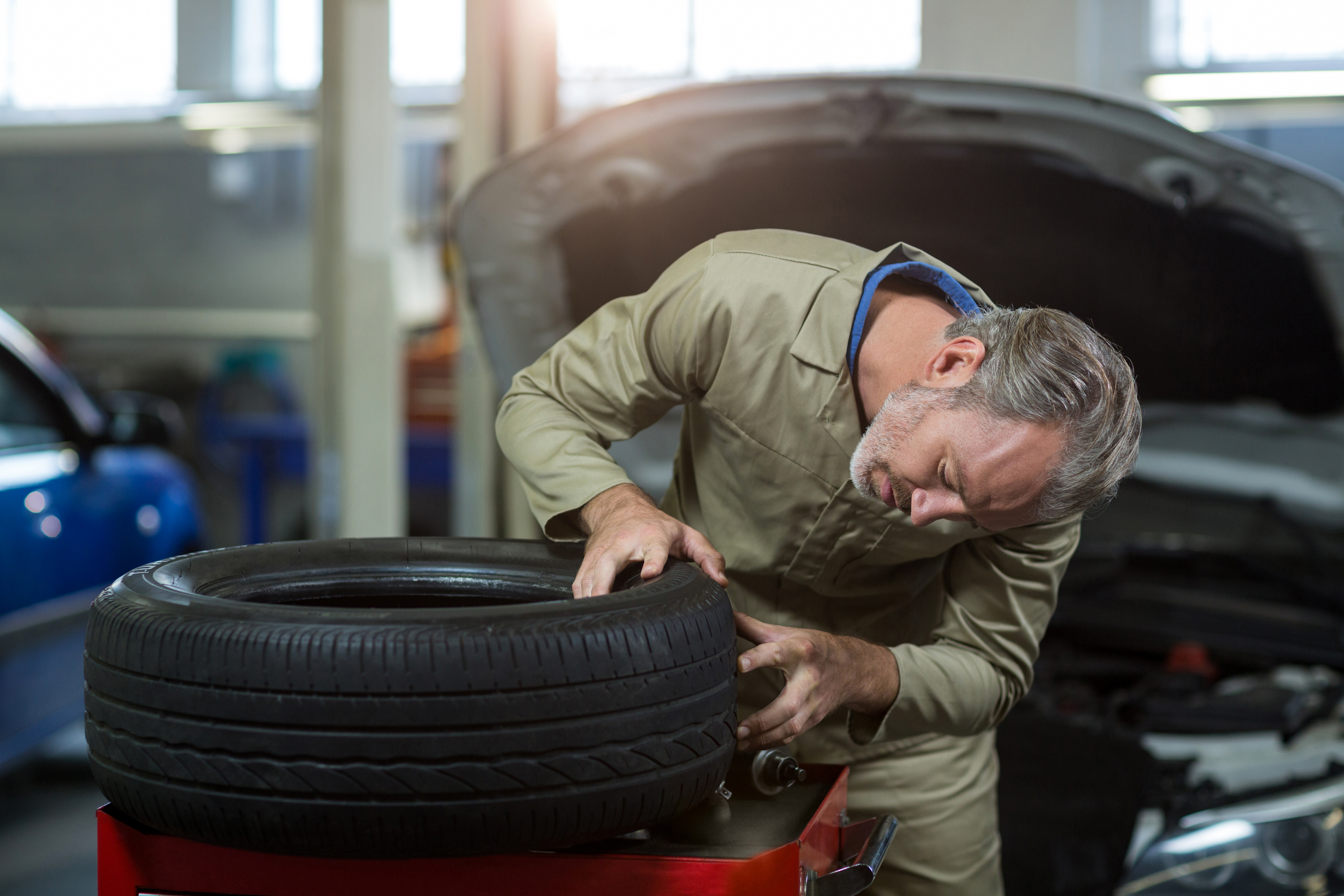 Mechanic examining a tyre in repair garage