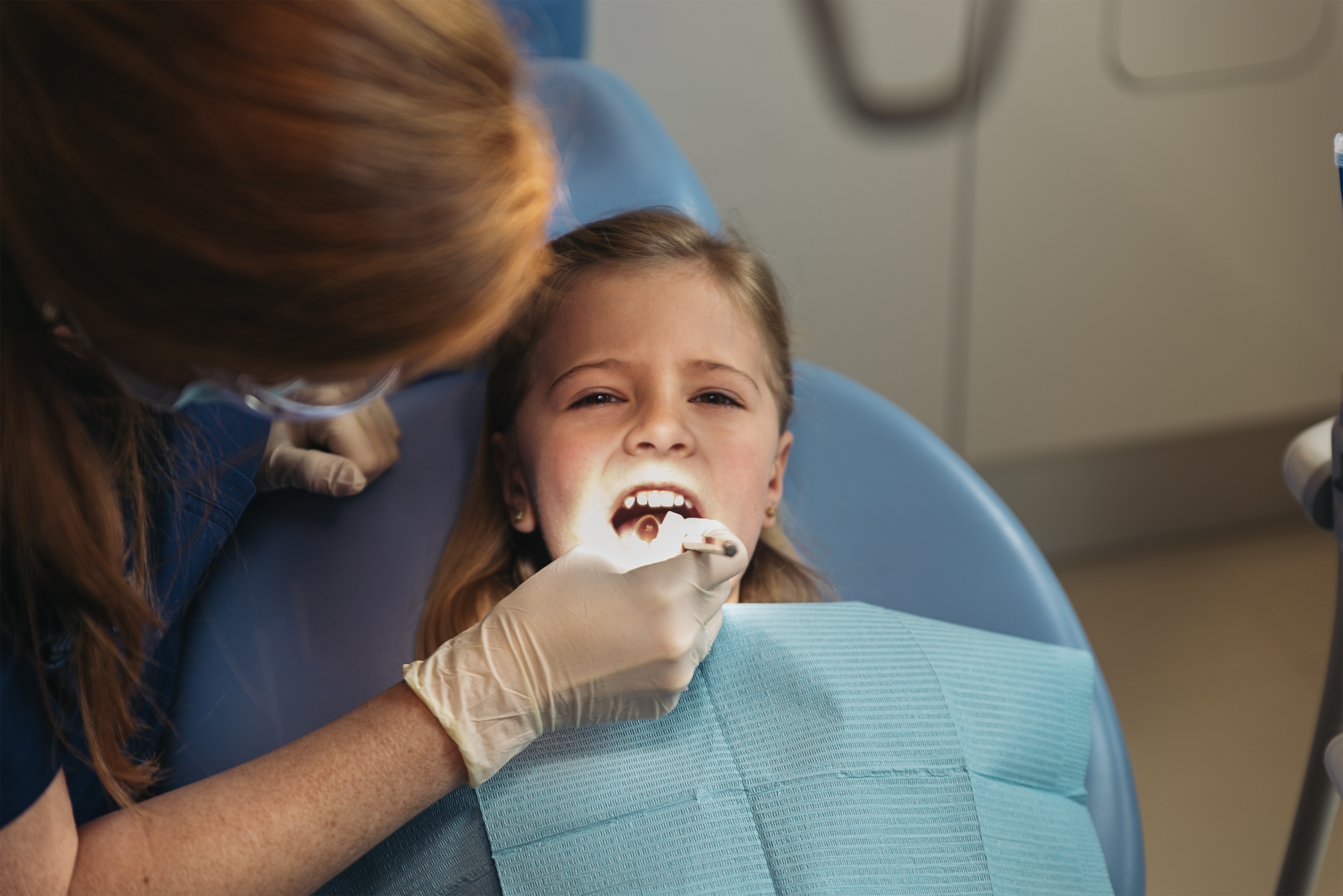 Dentists with a patient during a dental intervention to girl. Dentist Concept