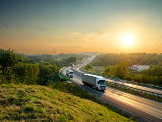White,Trucks,Driving,On,The,Highway,Winding,Through,Forested,Landscape